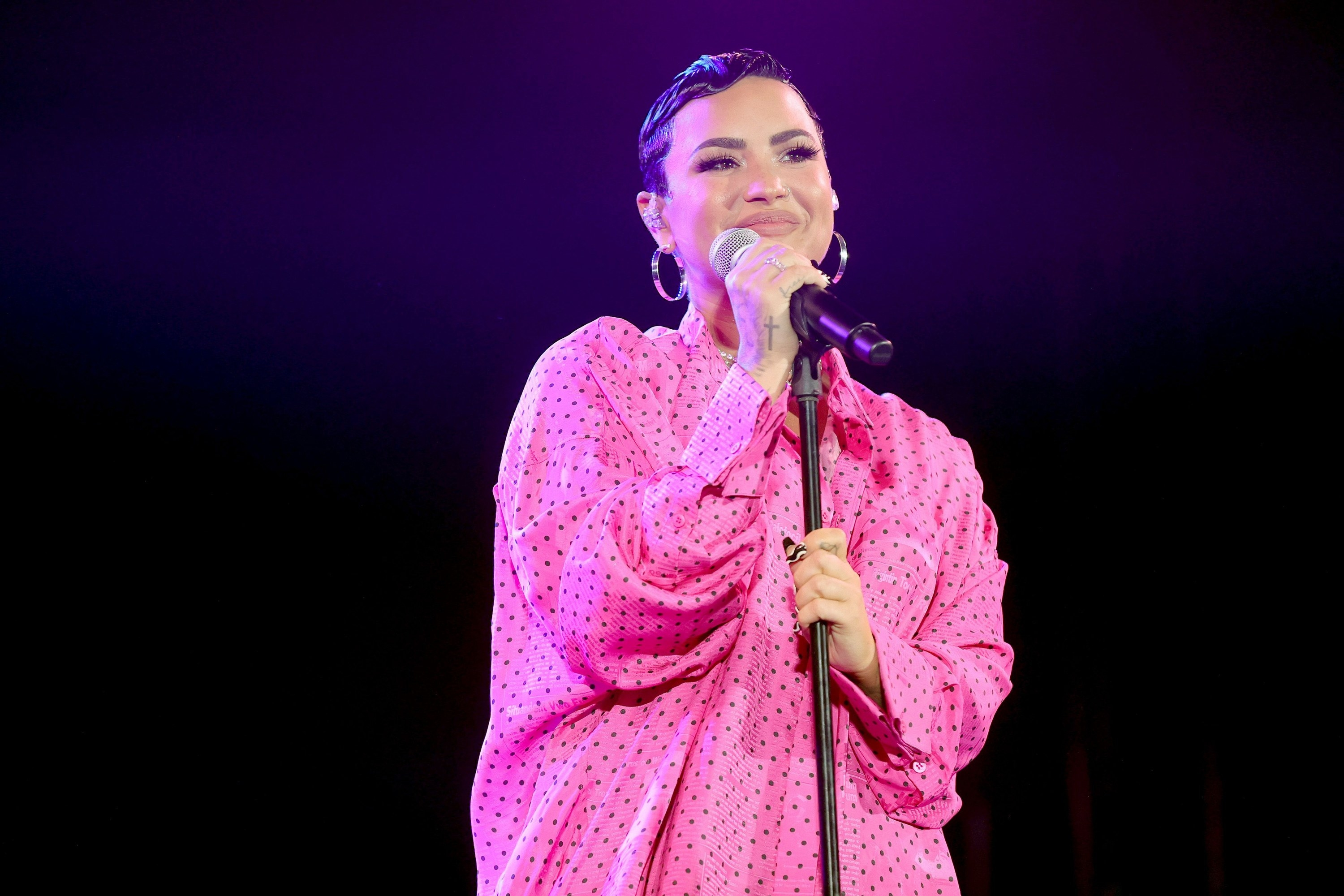 Demi performing on stage in a polka dot ensemble and rocking short hair