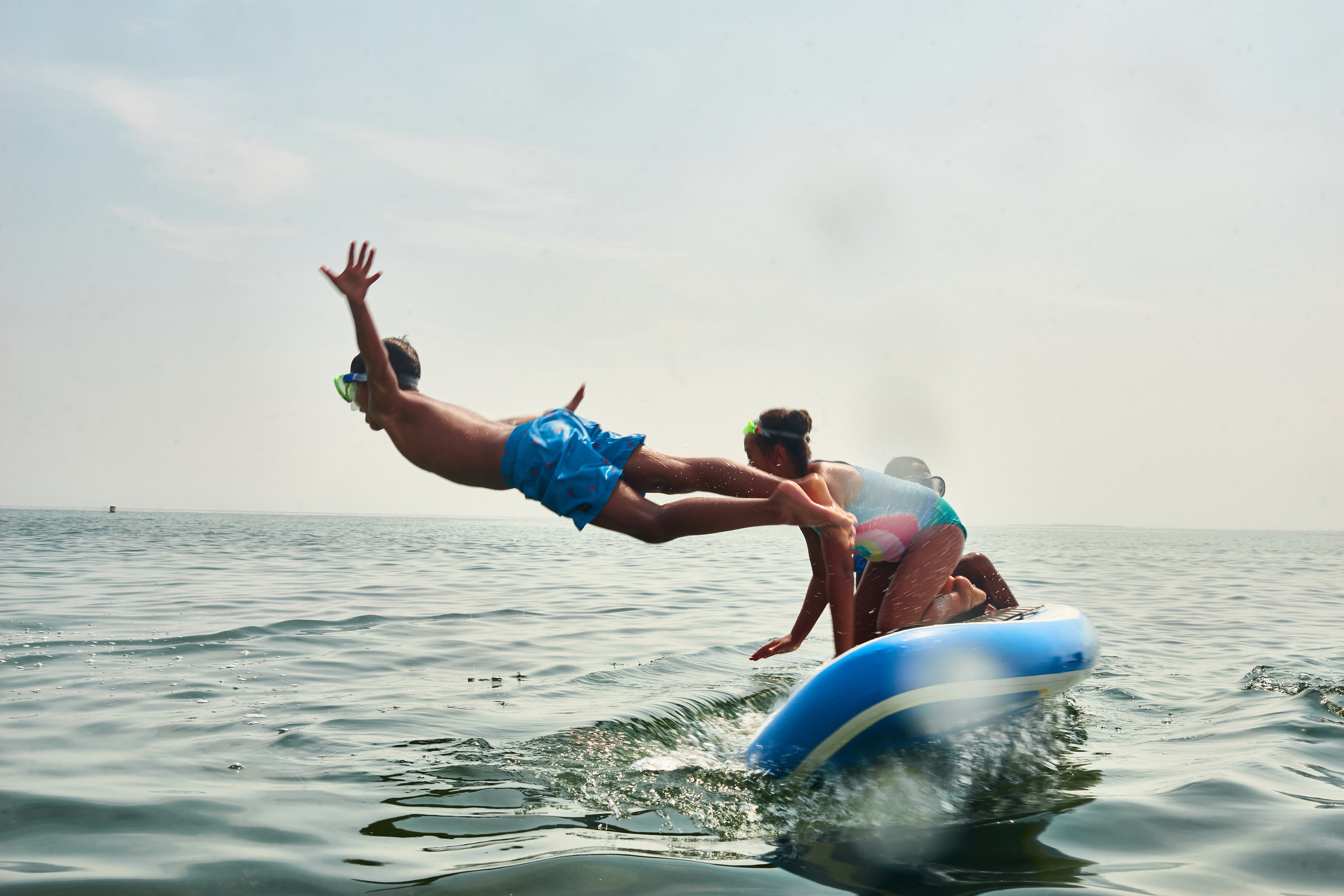 Children, one with goggles, prepare to jump into the water from a surfboard