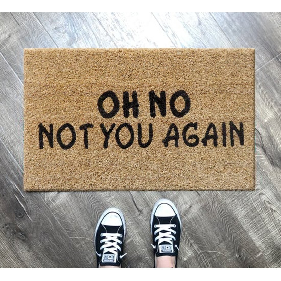 A fibre door mat in beige with the words - 'Oh no, not you again' on it