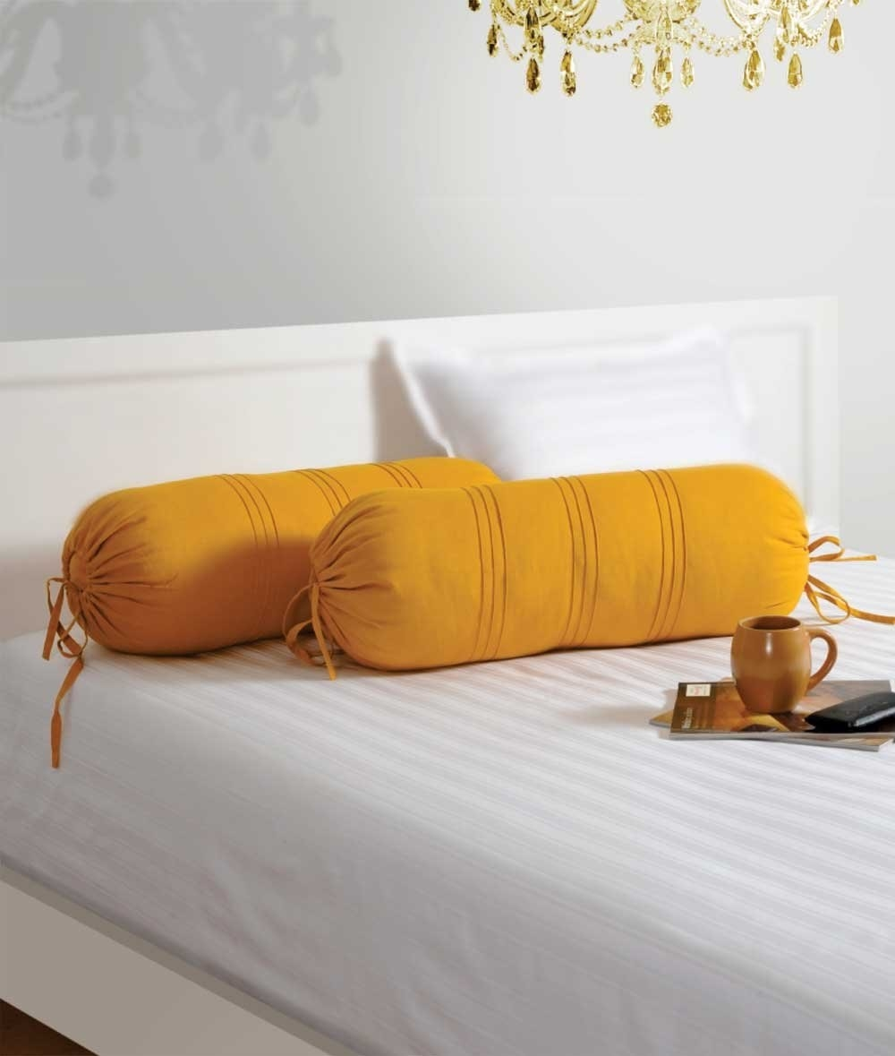 Two yellow bolster cushions kept on a white bed