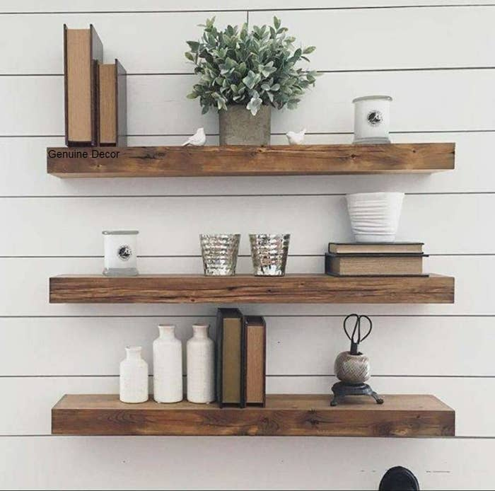 3 wooden wall mounted shelves with books, show pieces, candles and potted plants arranged