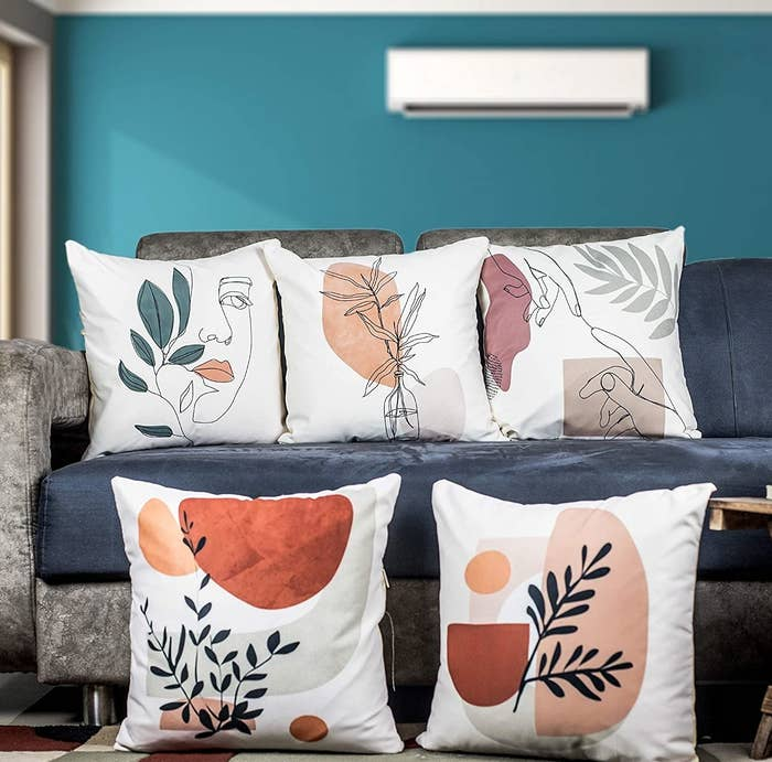 A set of 5 cushion covers with a white background and pretty shades, faces and leaves printed on it