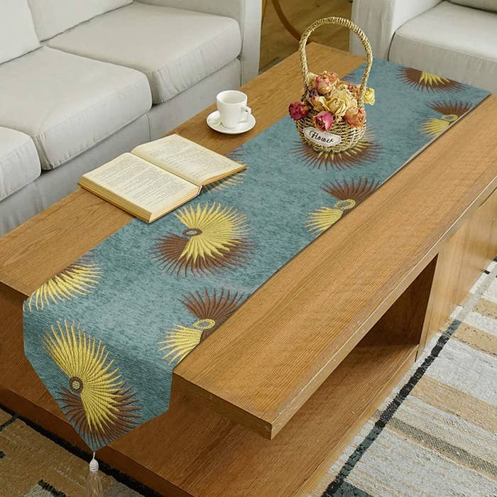 A cotton table runner in teal with yellow and ombre sun patterns embroidered on it