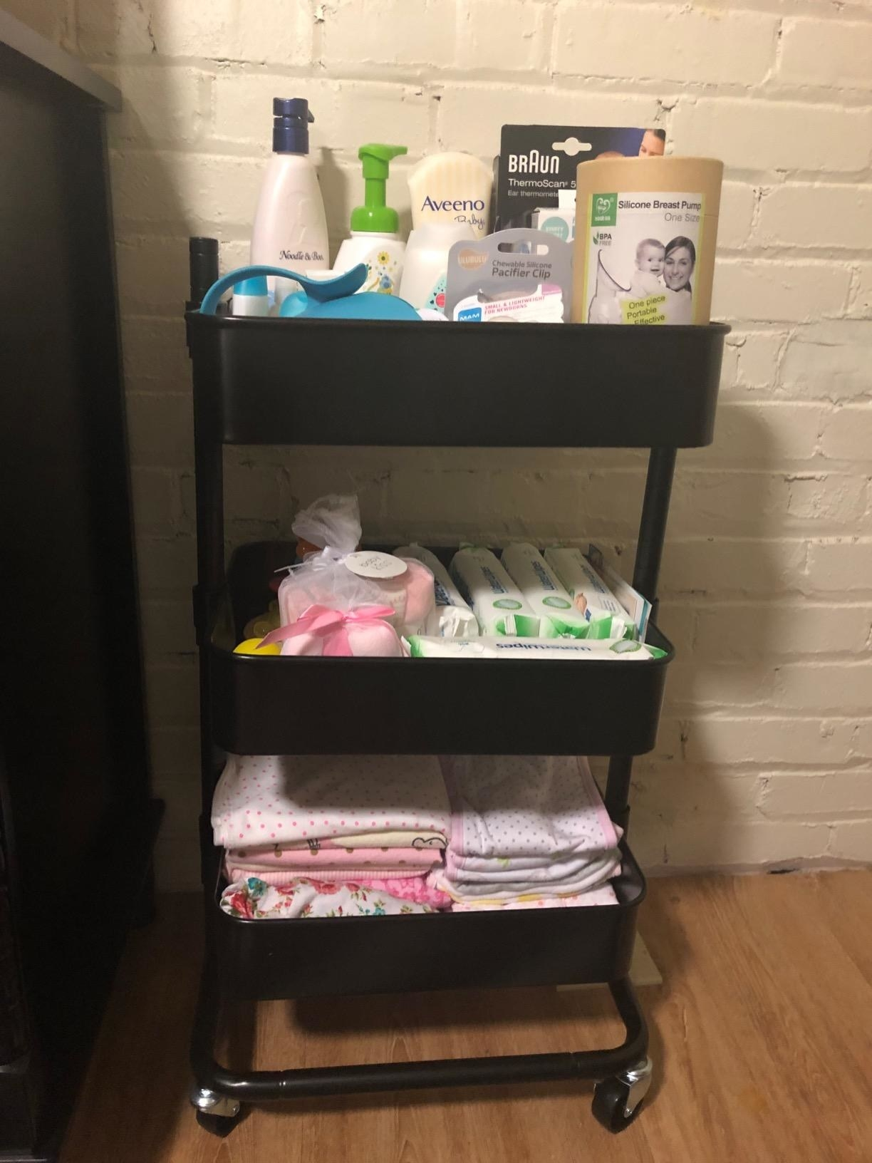 reviewer image of the black songmics utility cart with baby products in each of its three tiers