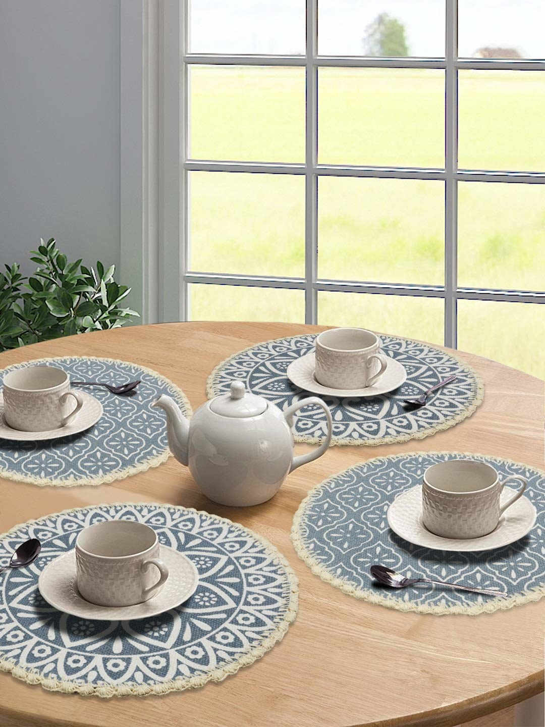 Circular Jute grey table mats with white porcelain cups placed on top of it