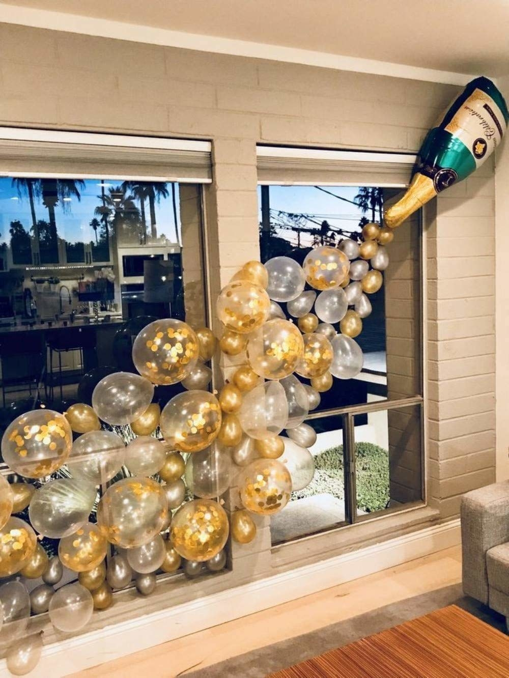 A champagne balloon with numerous smaller golden balloons coming out of it