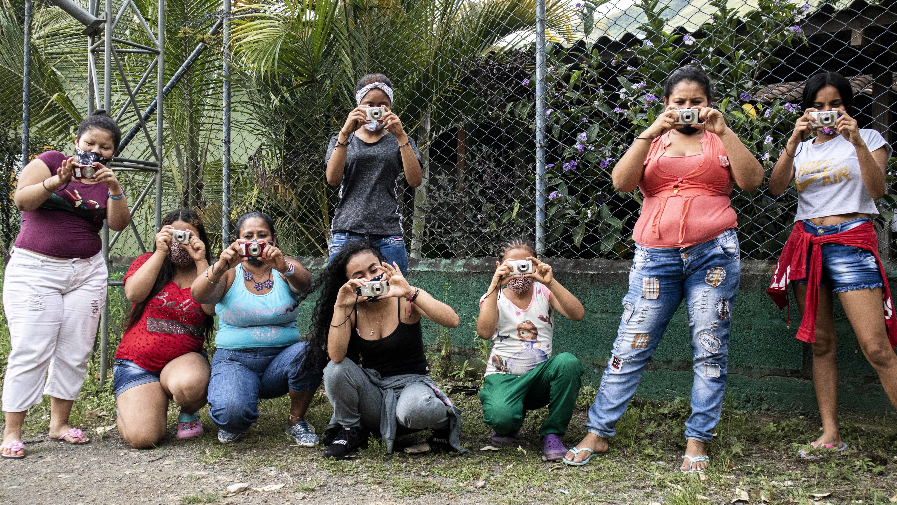 Eight women with cameras pointing them at the camera, wearing masks