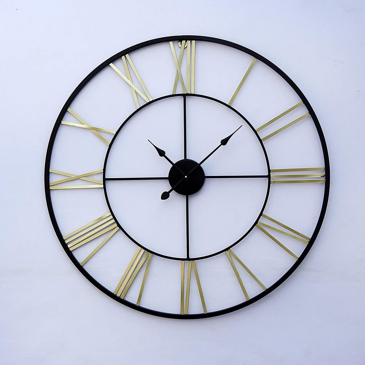 A large metal clock with a black frame and golden numericals, displayed against a white wall that works as its base
