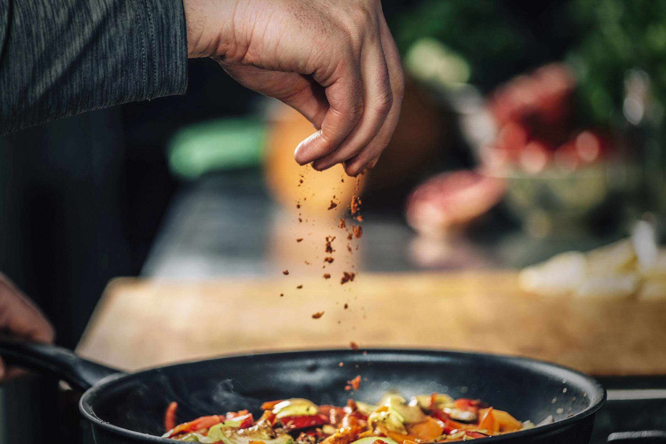 Sprinkling paprika over vegetables.