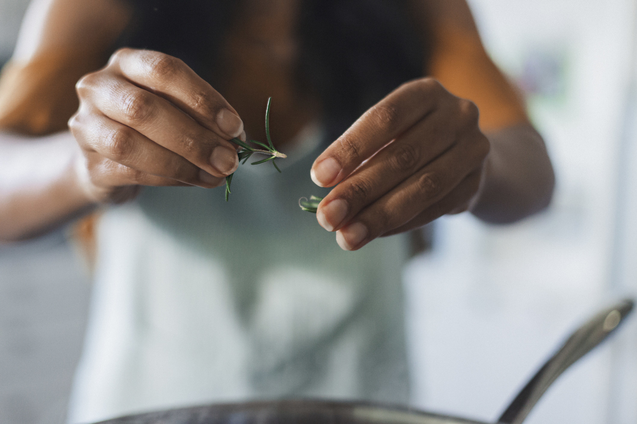 A woman putting fresh rosemary into food