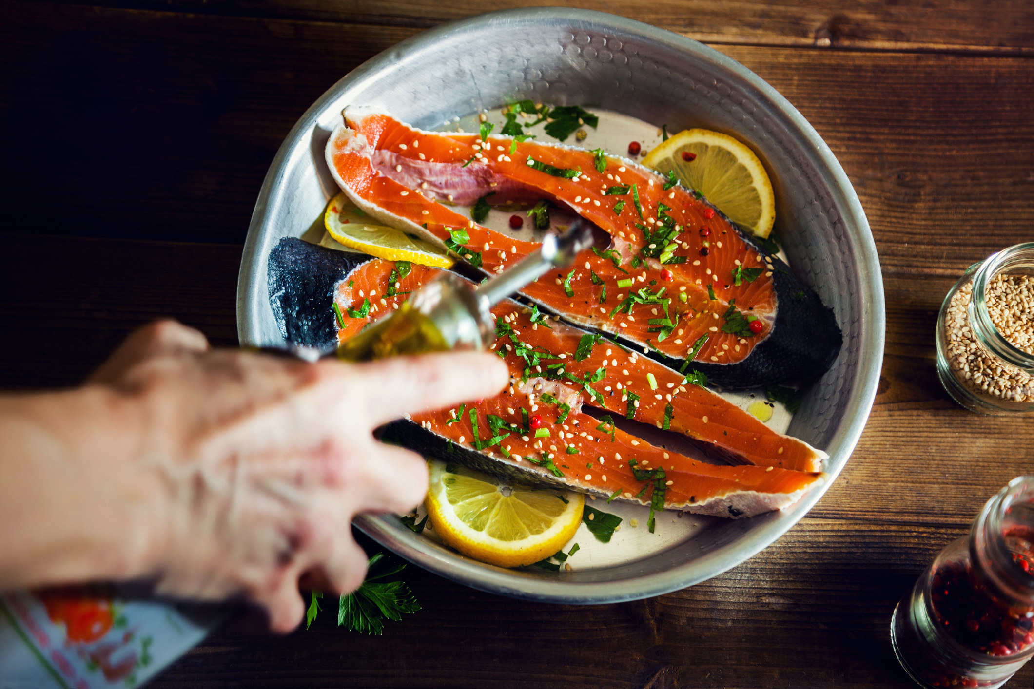 Seasoning salmon with olive oil.