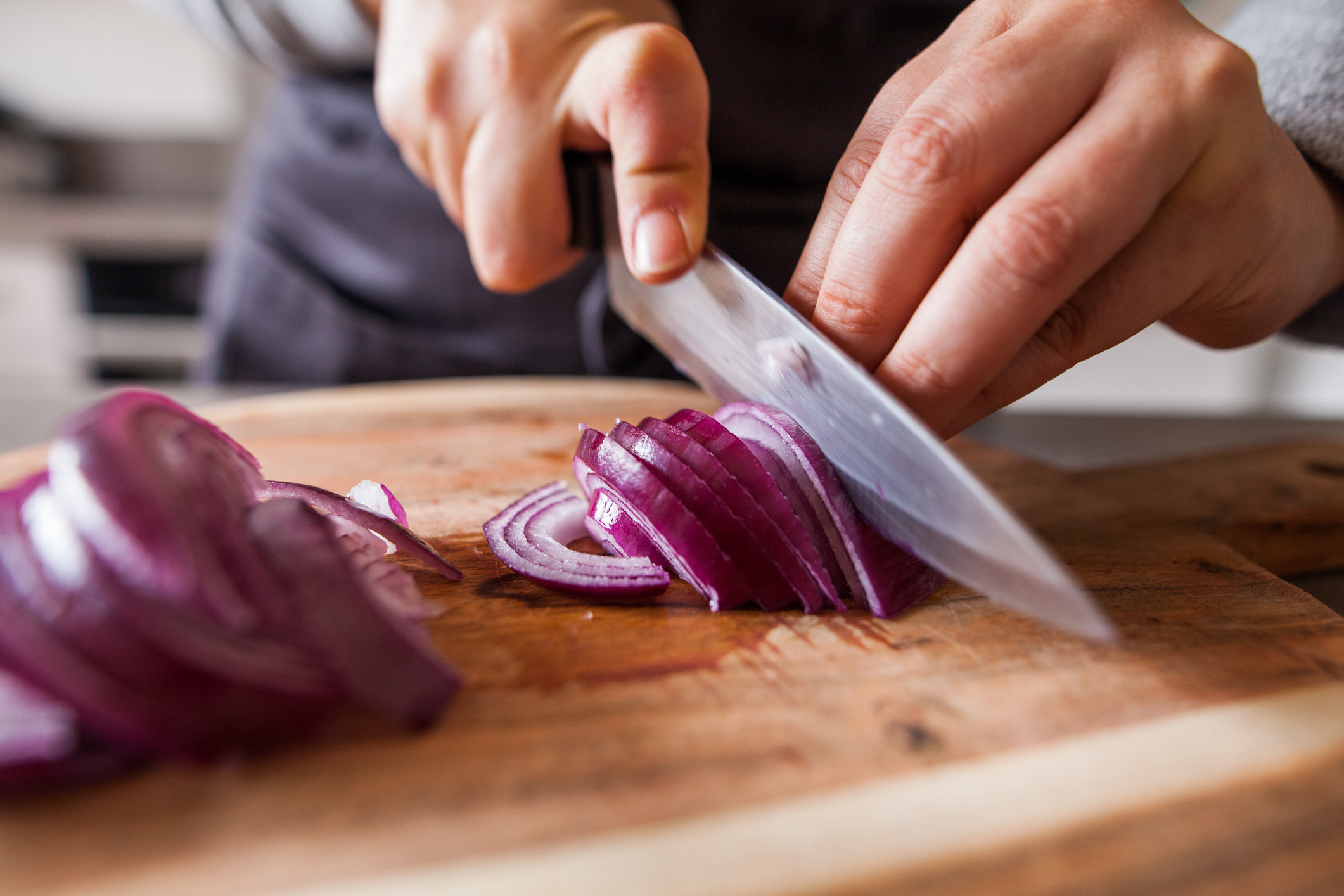 Slicing red onion with a sharp knife.