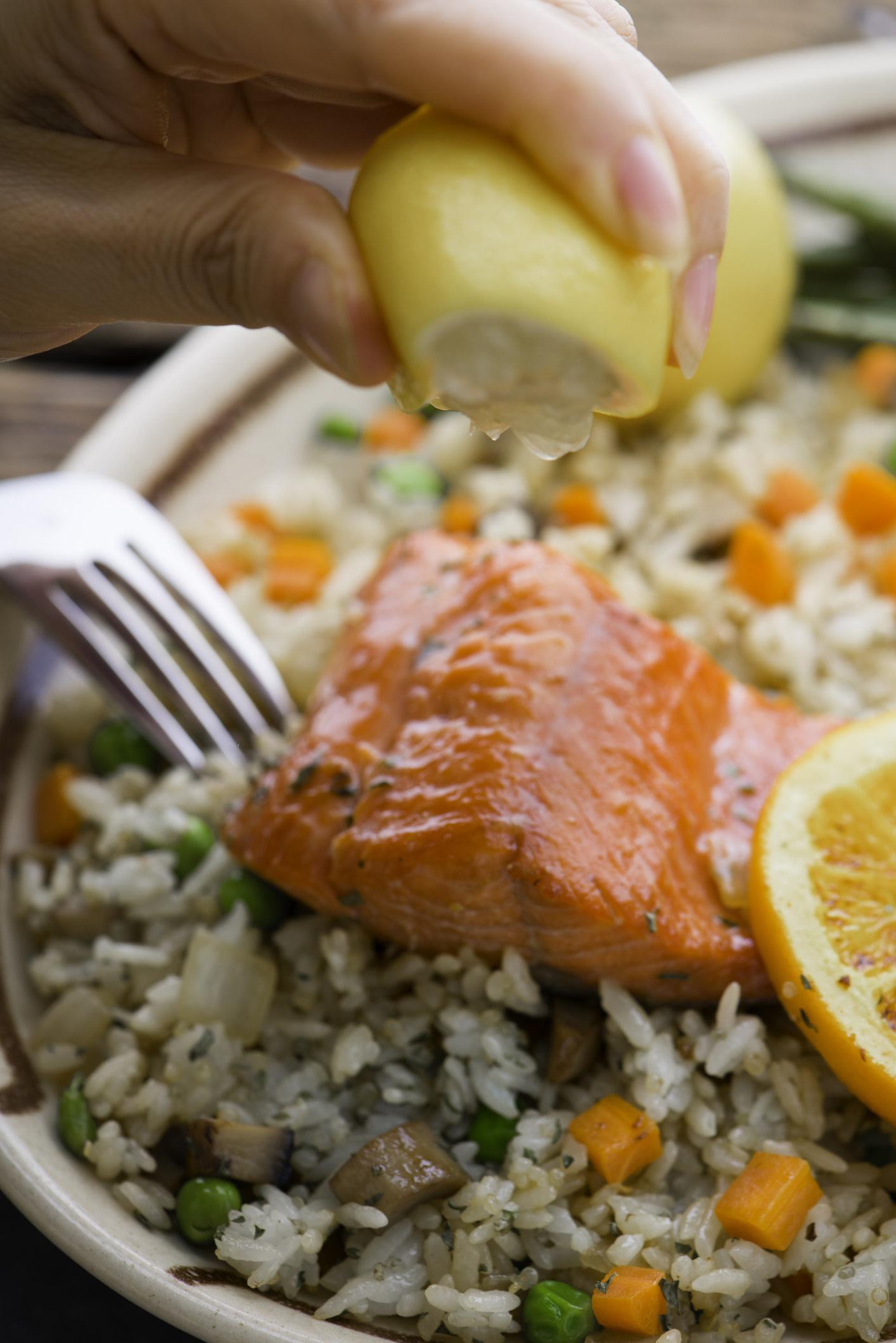 Squeezing lemon onto a piece of salmon