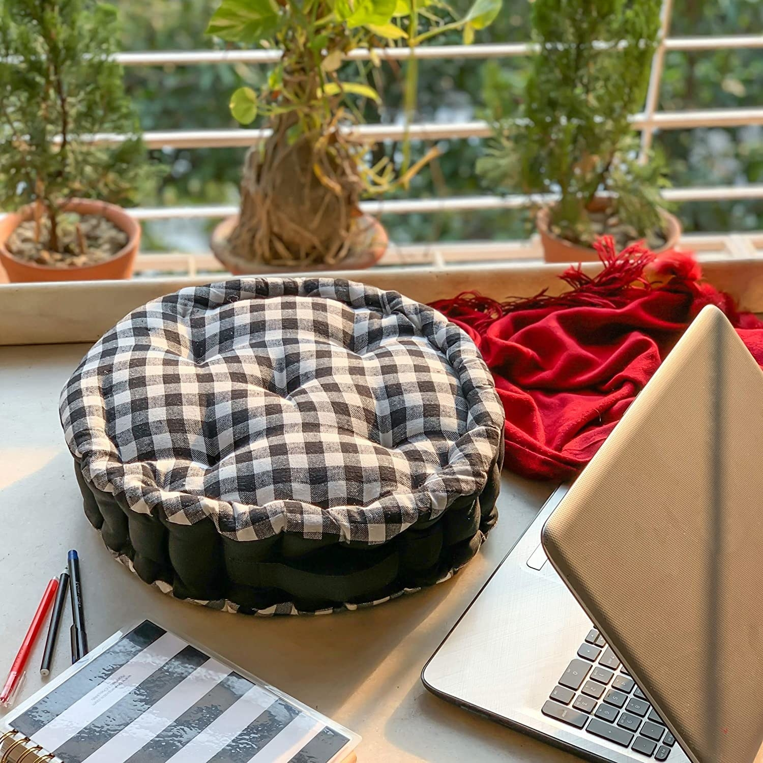 A checkered black and white round floor cushion kept on a balcony next to a laptop and notebook