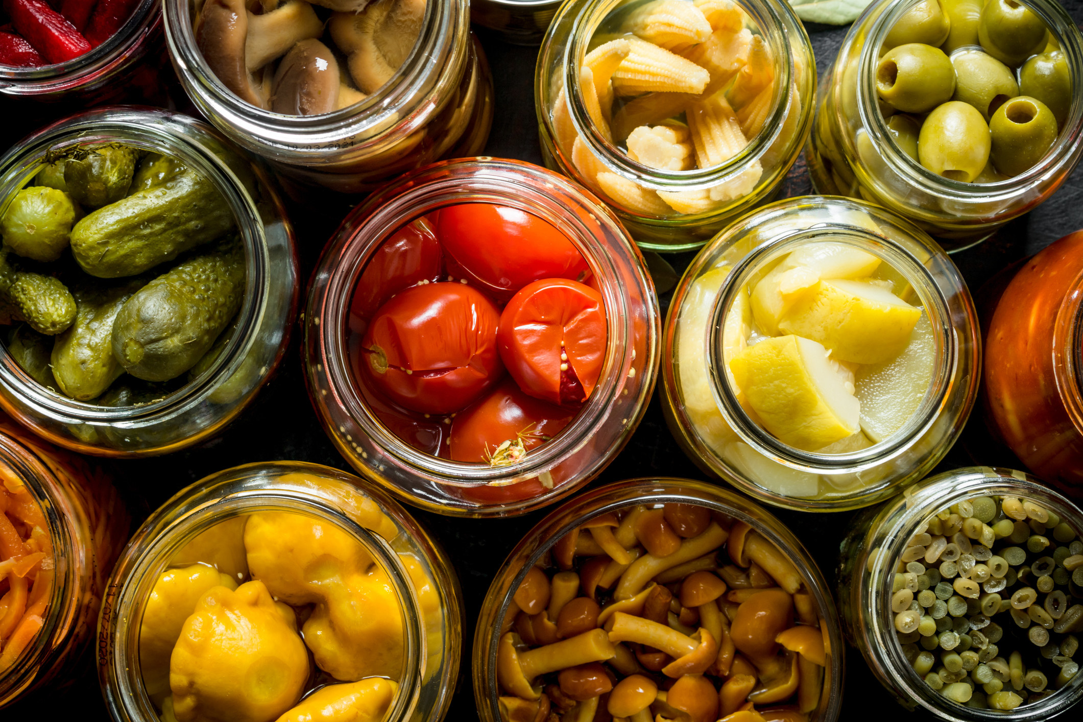 Different pickled veggies in glass jars.