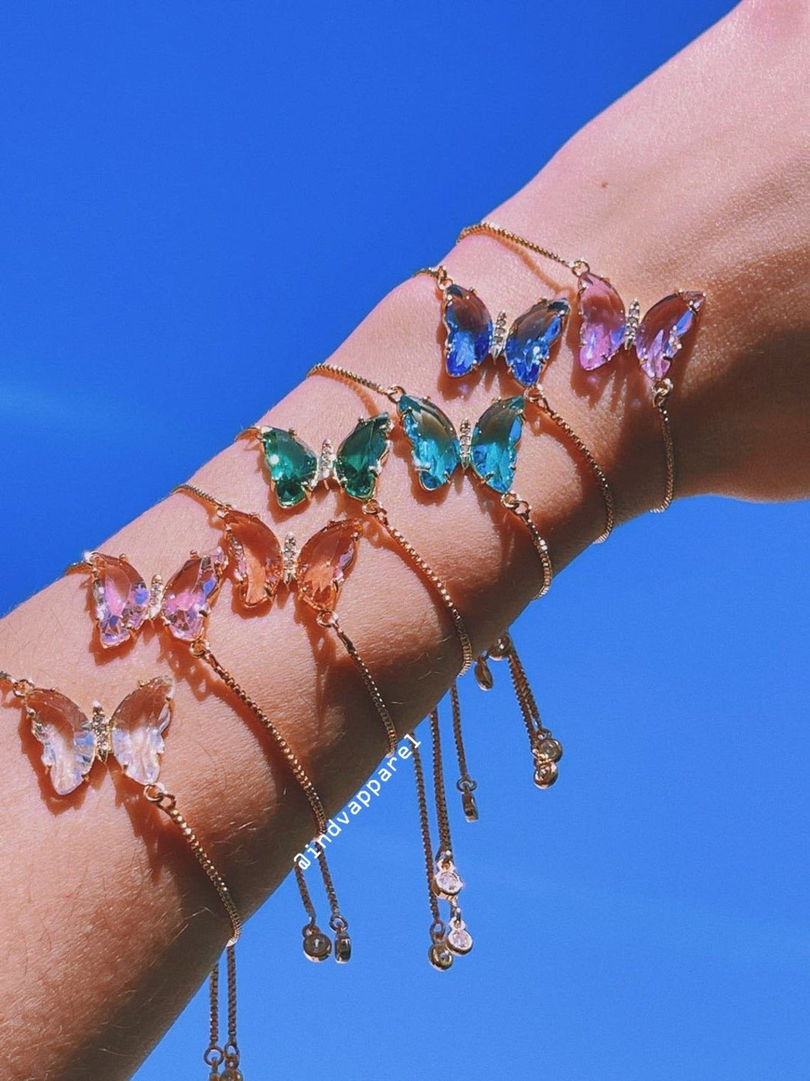an arm with a stack of butterfly bracelets on it