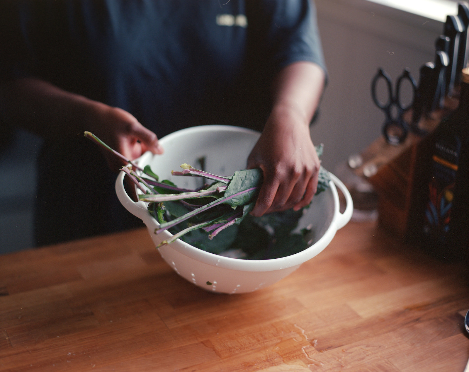Two hands holding a colander with kale