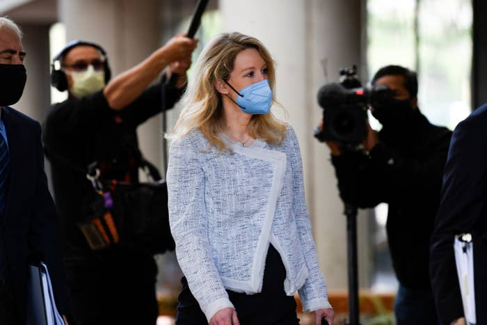 Holmes wears a face mask walks with several photographers behind her