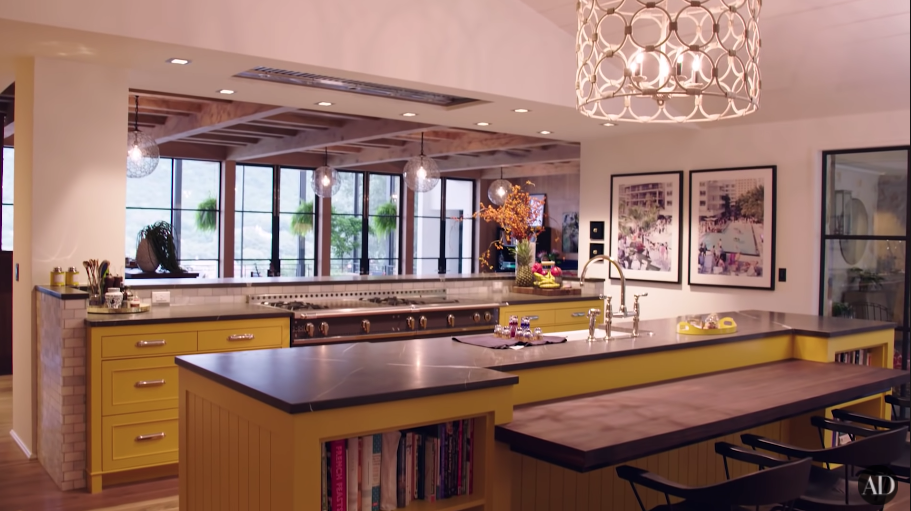 Another view of their large kitchen with paintings, large island table, and another room beyond it