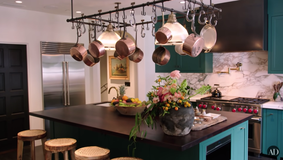 Another view of Kendall's kitchen with pots and pans hanging above an island table with stools
