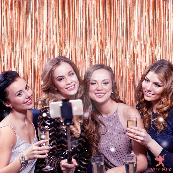 4 women standing in front of a rose gold foil curtain clicking selfies