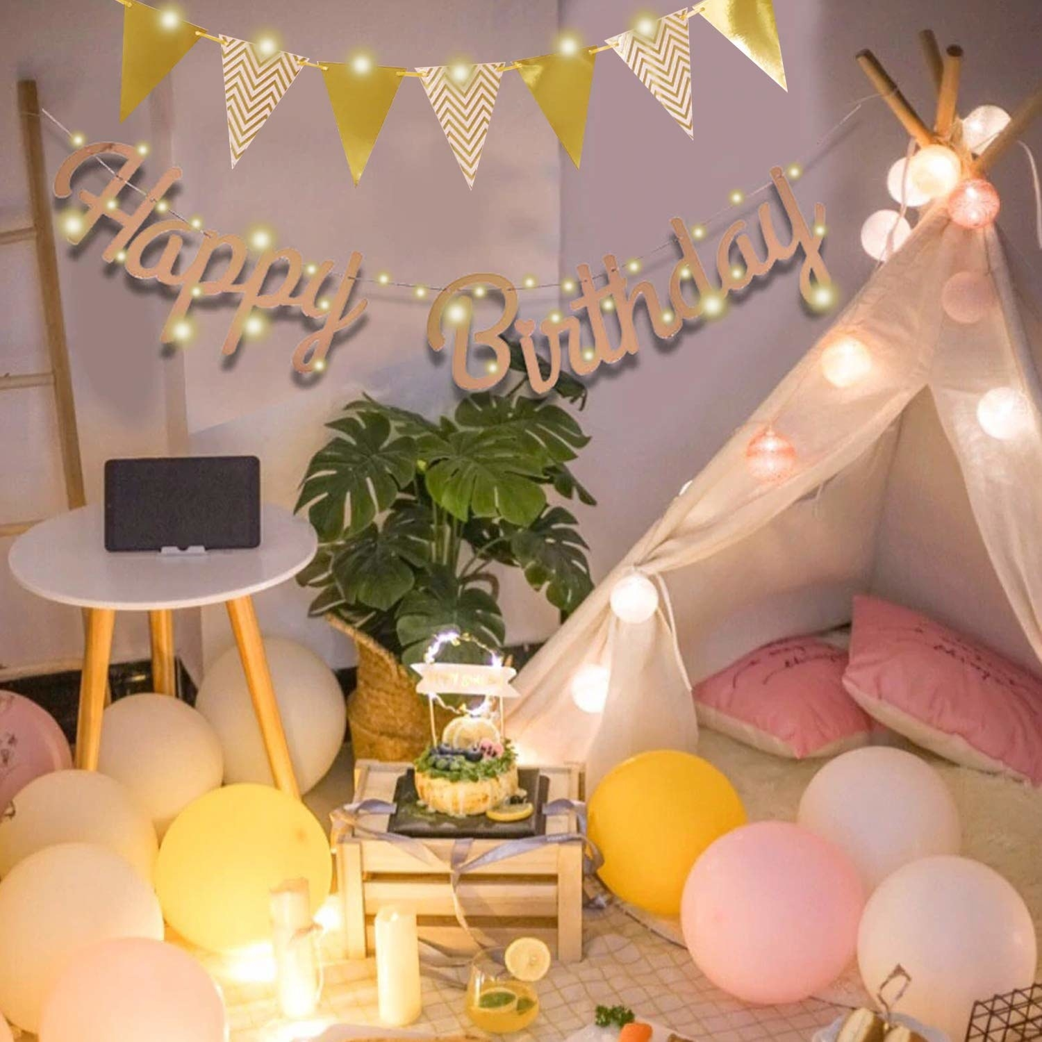 A room decorated with balloons, string lights and an LED 'Happy Birthday' banner
