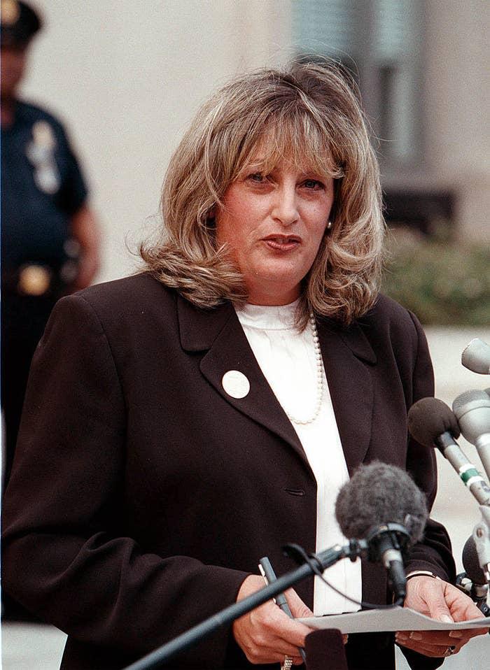 Linda Tripp speaking into several microphones