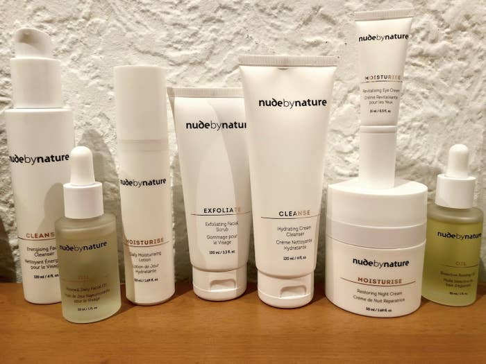 A line up of Nude By Nature skincare products including (from left to right): Energising Cleanser, Daily Facial Oil, Daily Moisturising Lotion, Exfoliating Scrub, Hydrating Cream Cleanser, Revitalising Eye Cream, Restoring Night Cream and Rosehip Oil