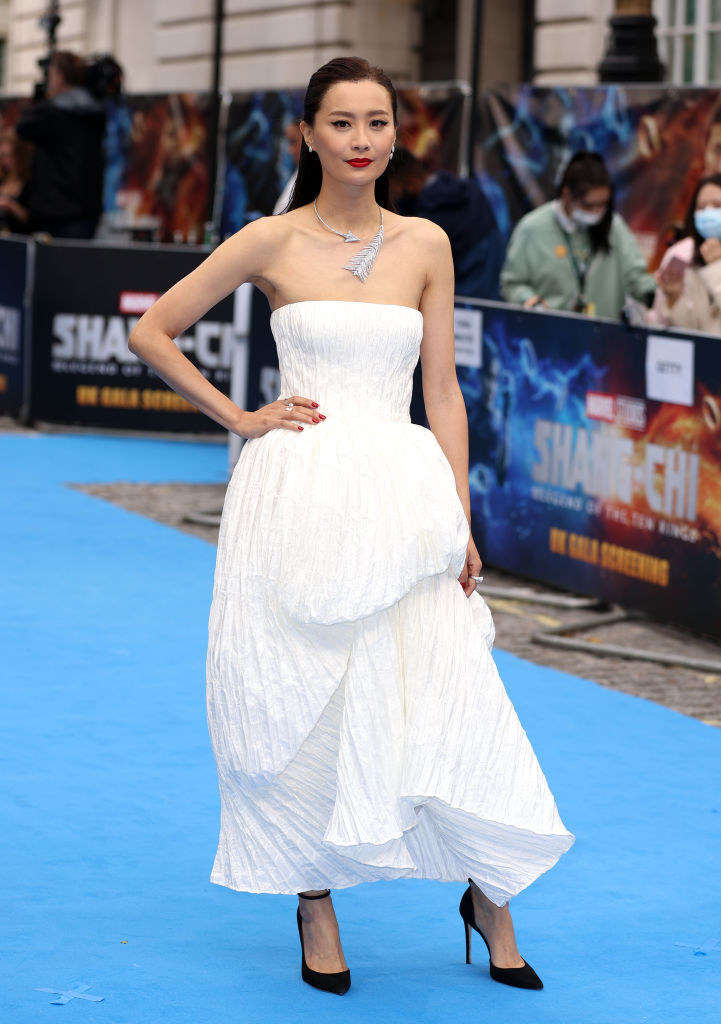 Fala Chen on the red carpet in a long, strapless white dress, standing with hand on hip