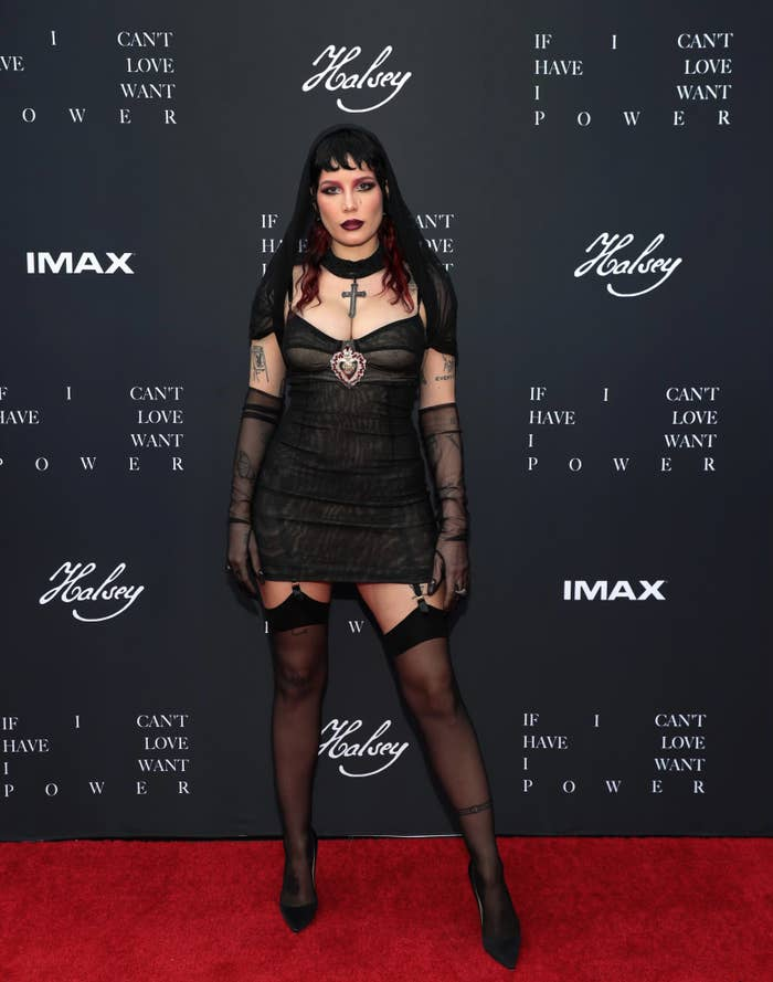 Halsey on the red carpet in all black: cross necklace, stockings with garter, minidress, high heels, and long, sheer gloves