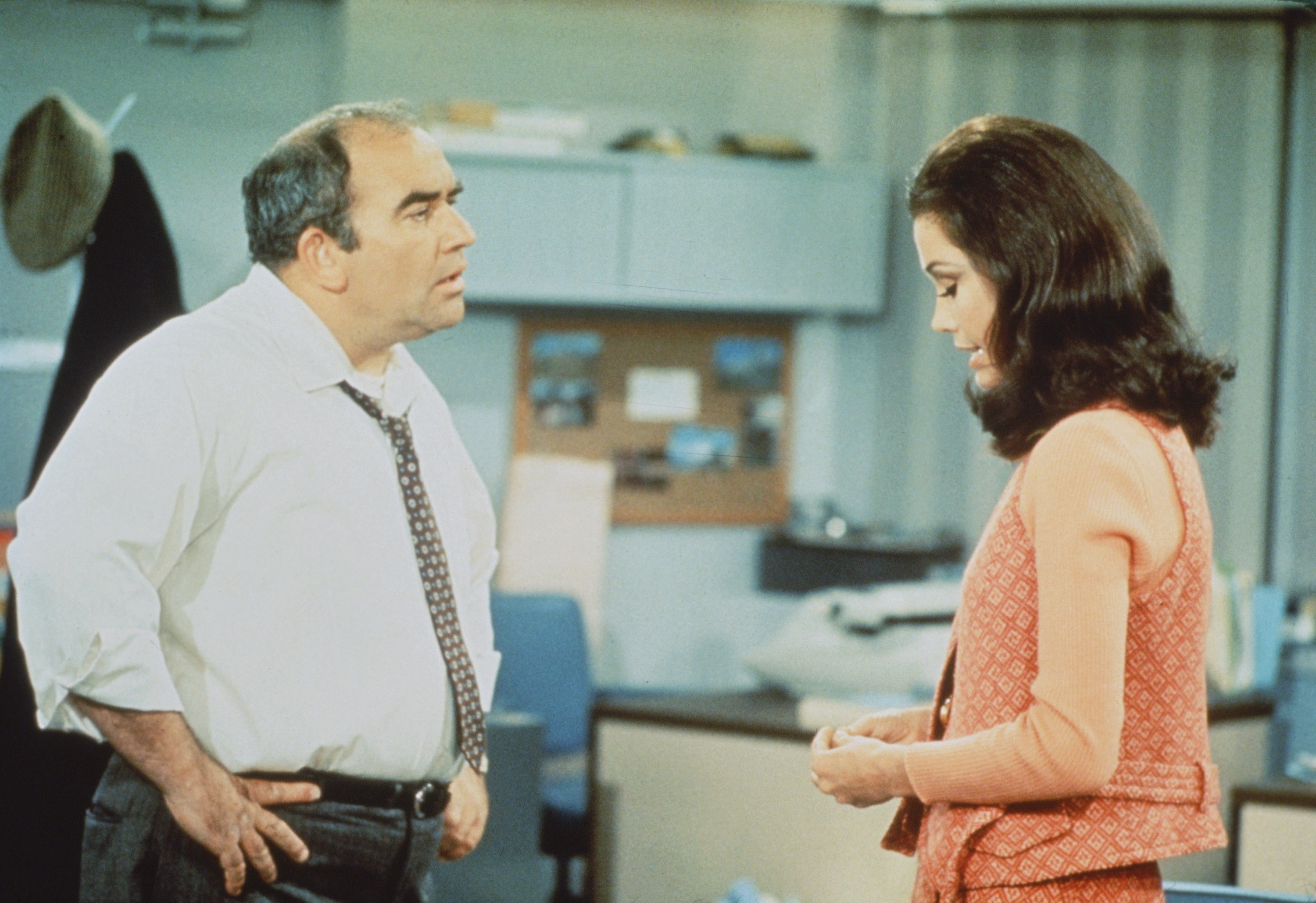 Ed with his hands on his hips talks to Mary, who's looking down, in the office