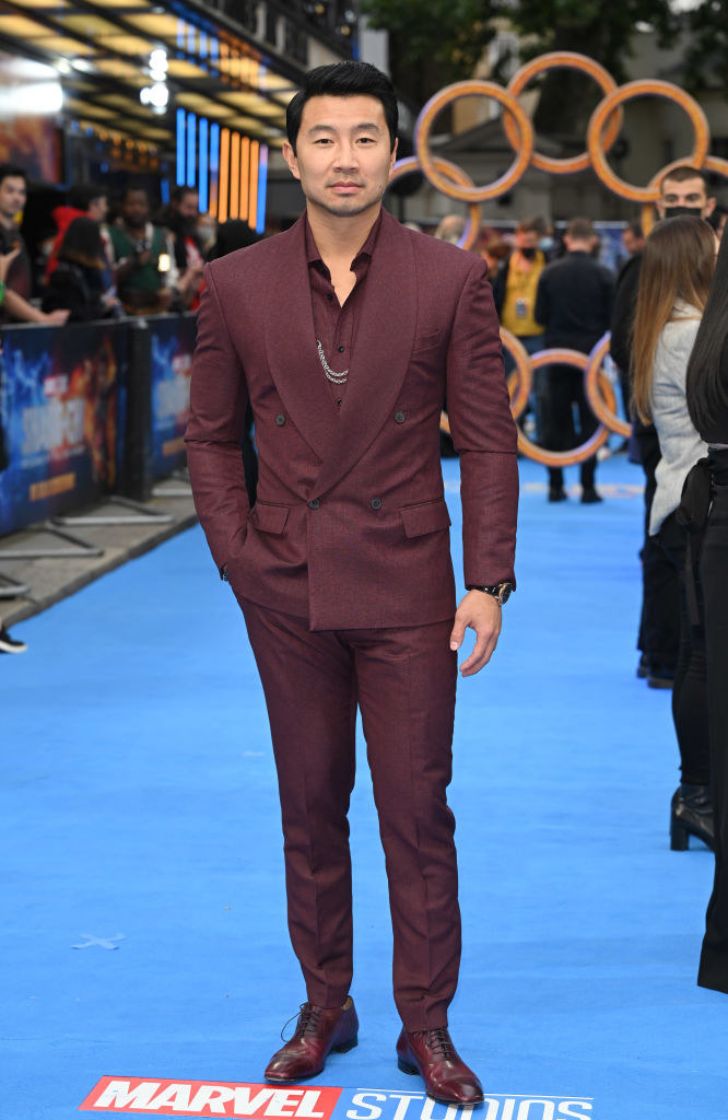 Simu Liu on the red carpet in a suit with hand in pants pocket