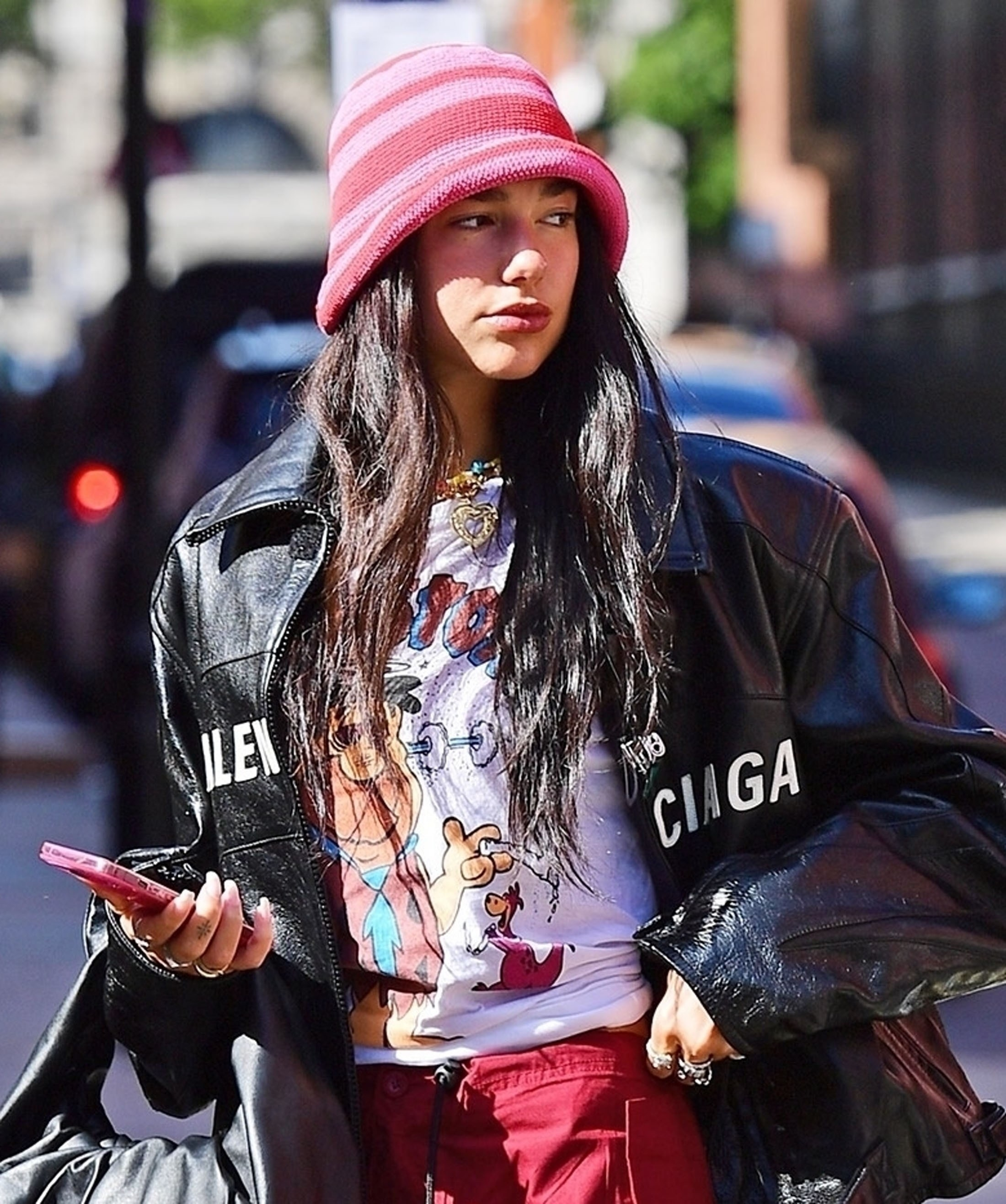 Dua looking to the side while wearing a black jacket and cartoon T-shirt and holding a cellphont