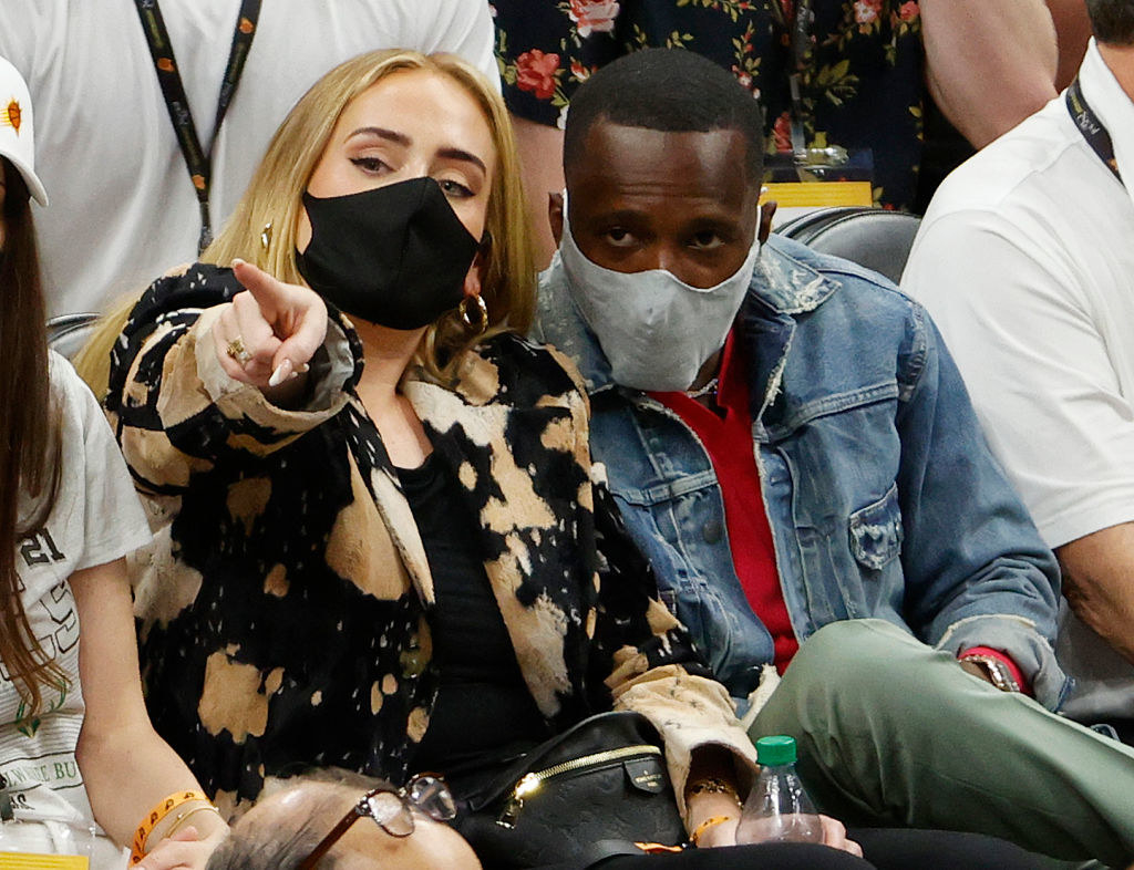 Adele, pointing at something, sits with Rich Paul, both masked, in the stands during Game 5 of the NBA Finals