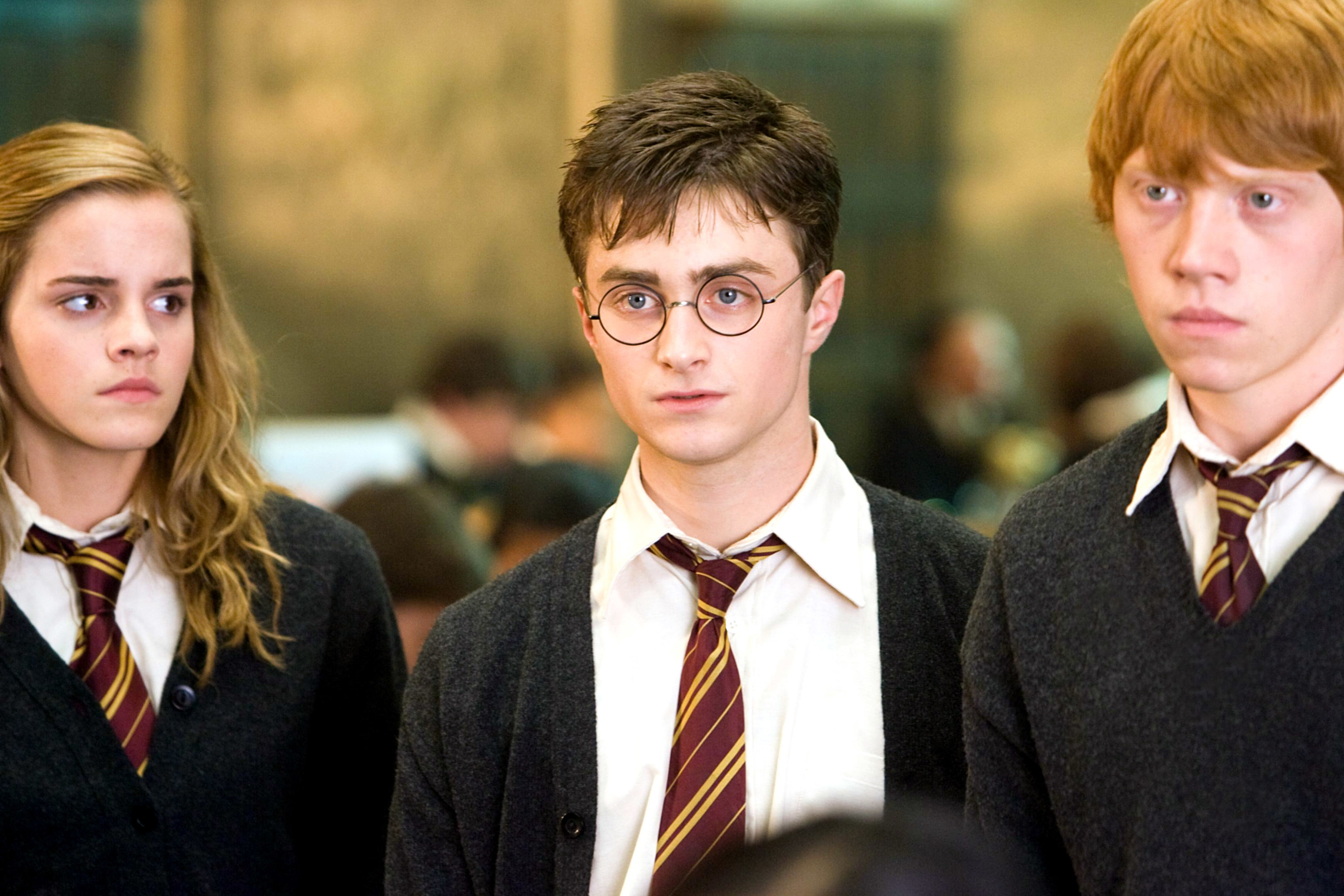 Radcliffe stands next to his costars Emma Watson and Rupert Grint in their Hogwarts uniforms