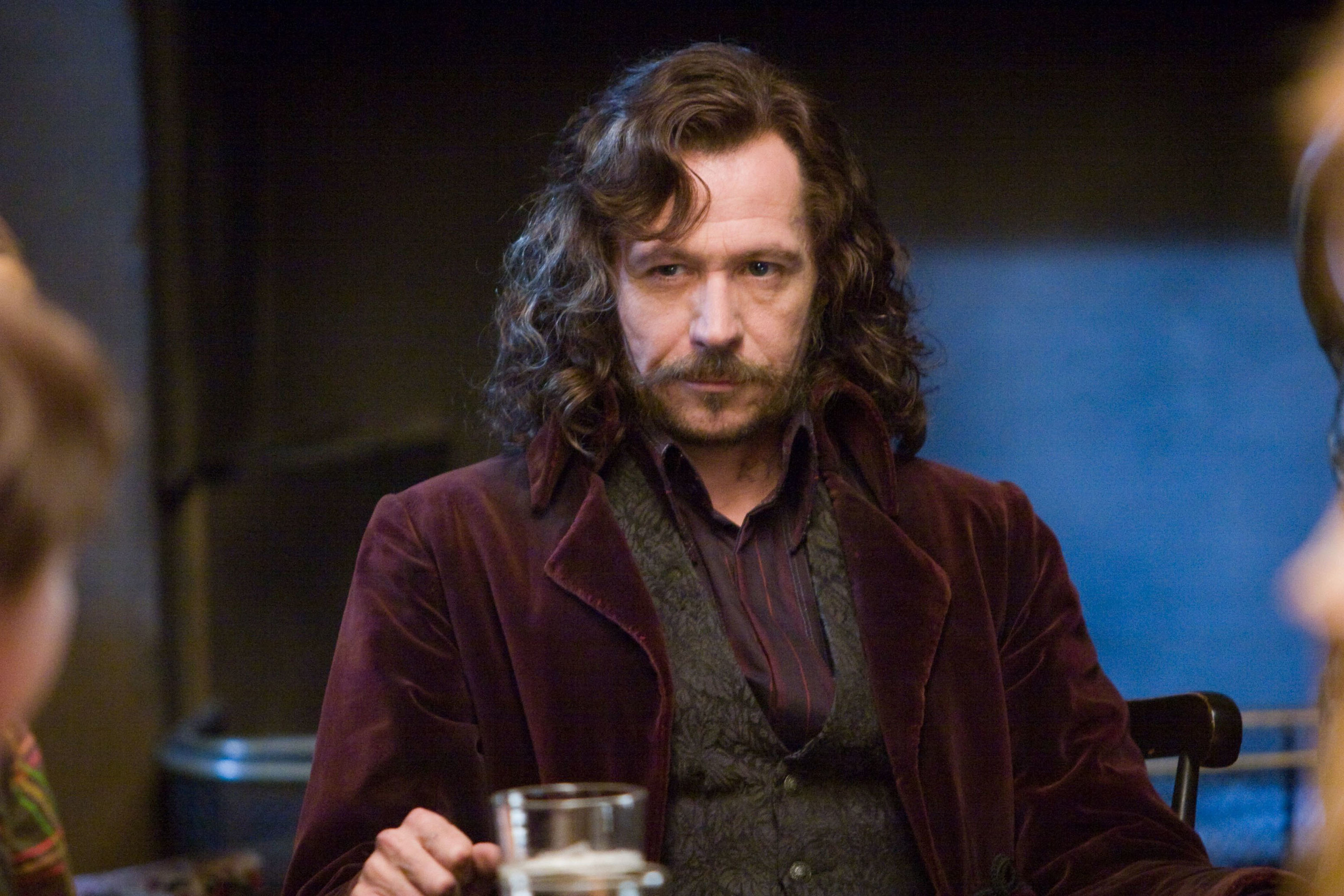 Gary Oldman sits at a table while looking at another character with a glass in front of him