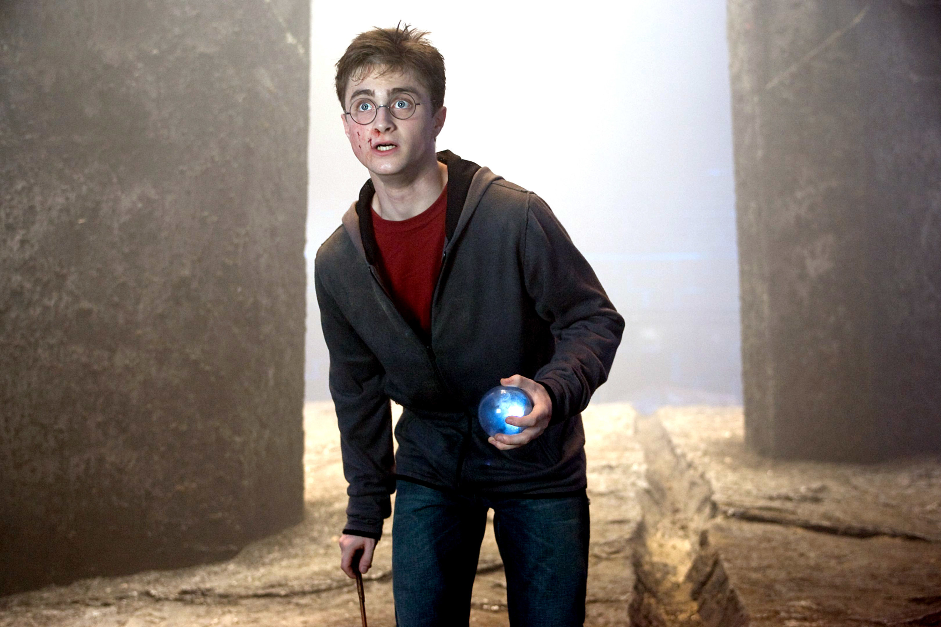 Radcliffe clutches an orb and brandishes his wand at his side as Harry Potter
