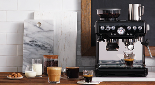 A kitchen countertop with a Breville espresso machine and two cups of coffee and two espresso shots alongside a jar of coffee beans and two glasses of milk.