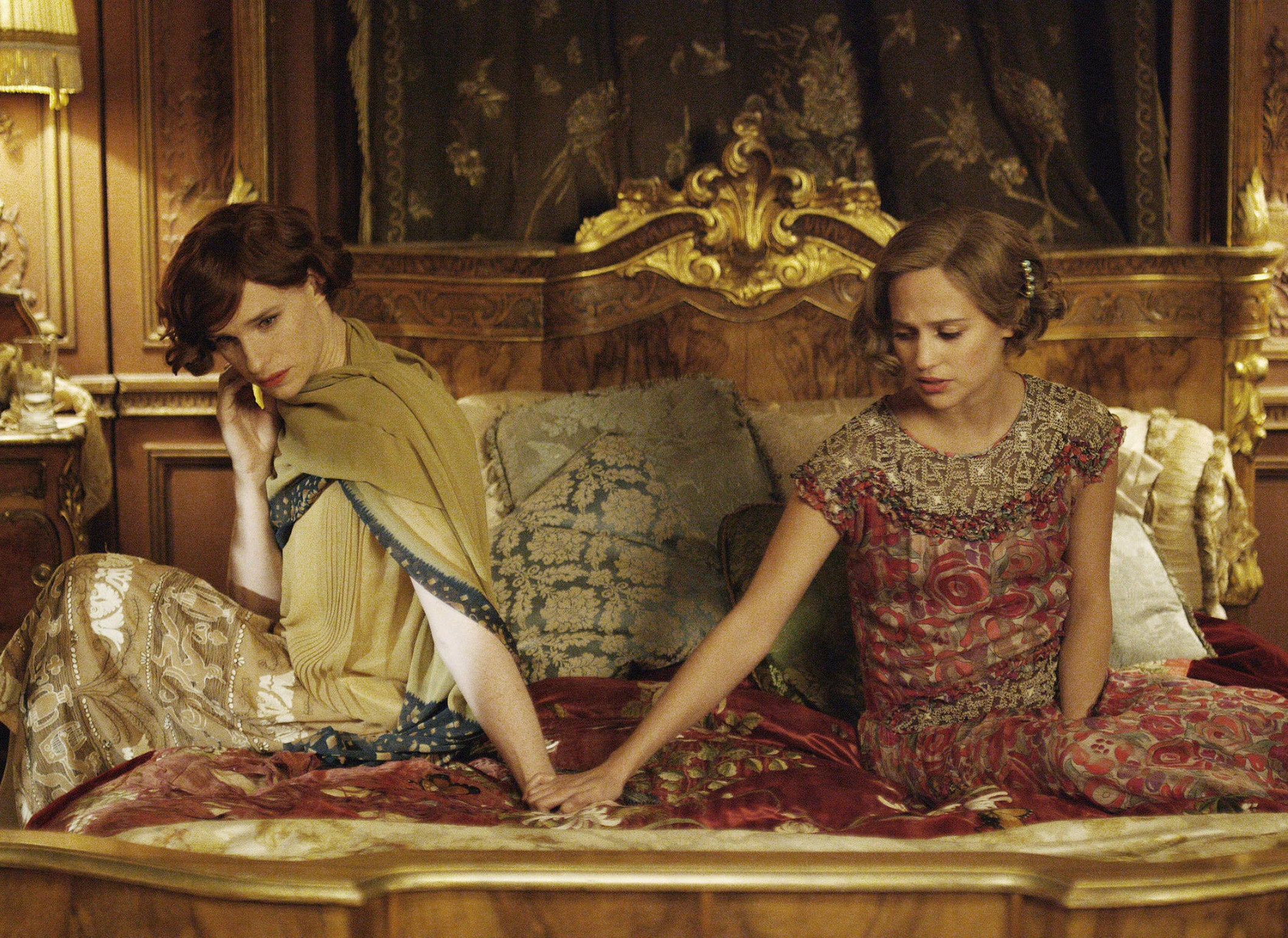 Einar, in women's clothing, sits on a bed next to Gerda