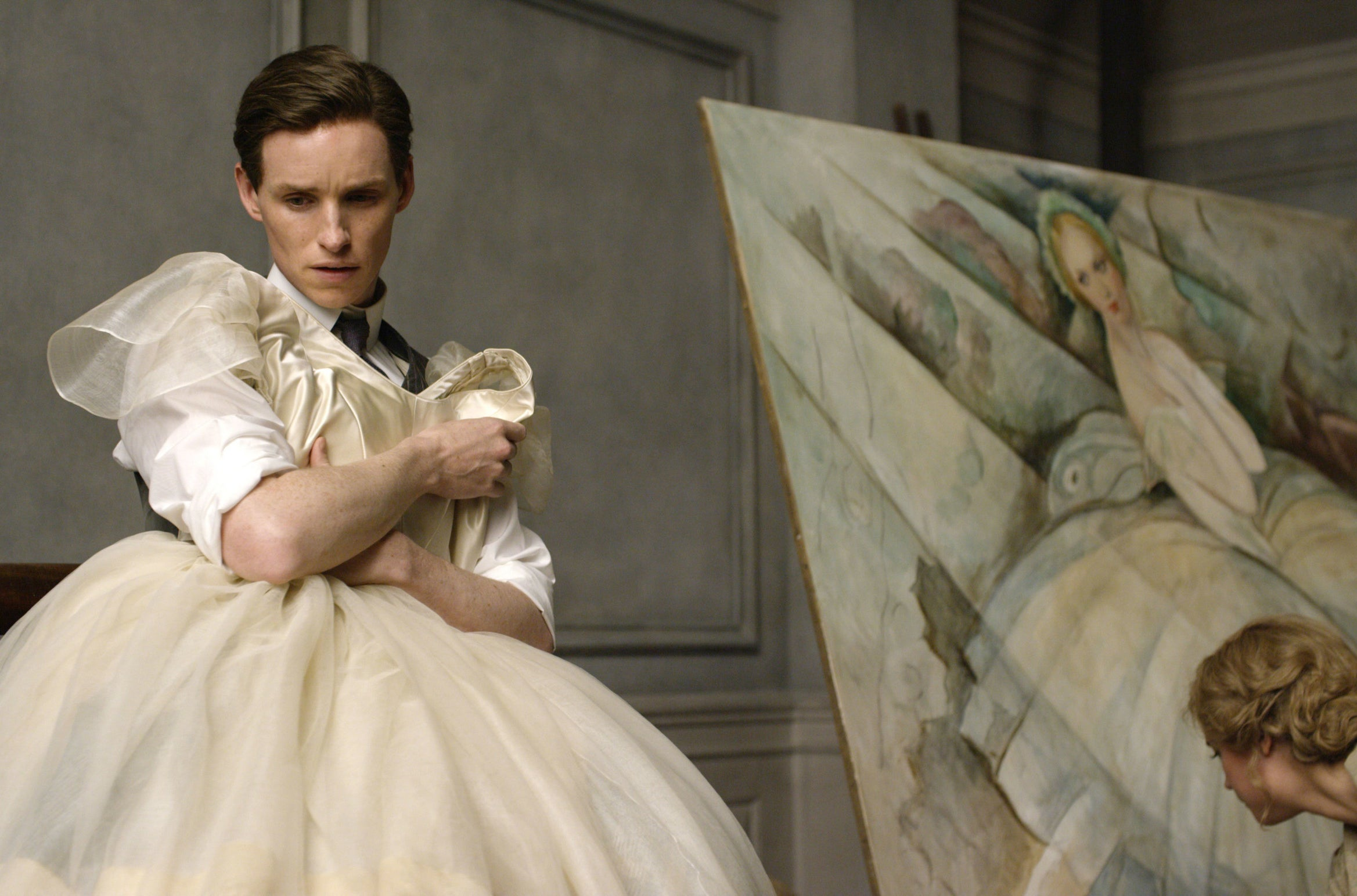 Einar, in a suit, holds up a dress in front of themselves while being painted