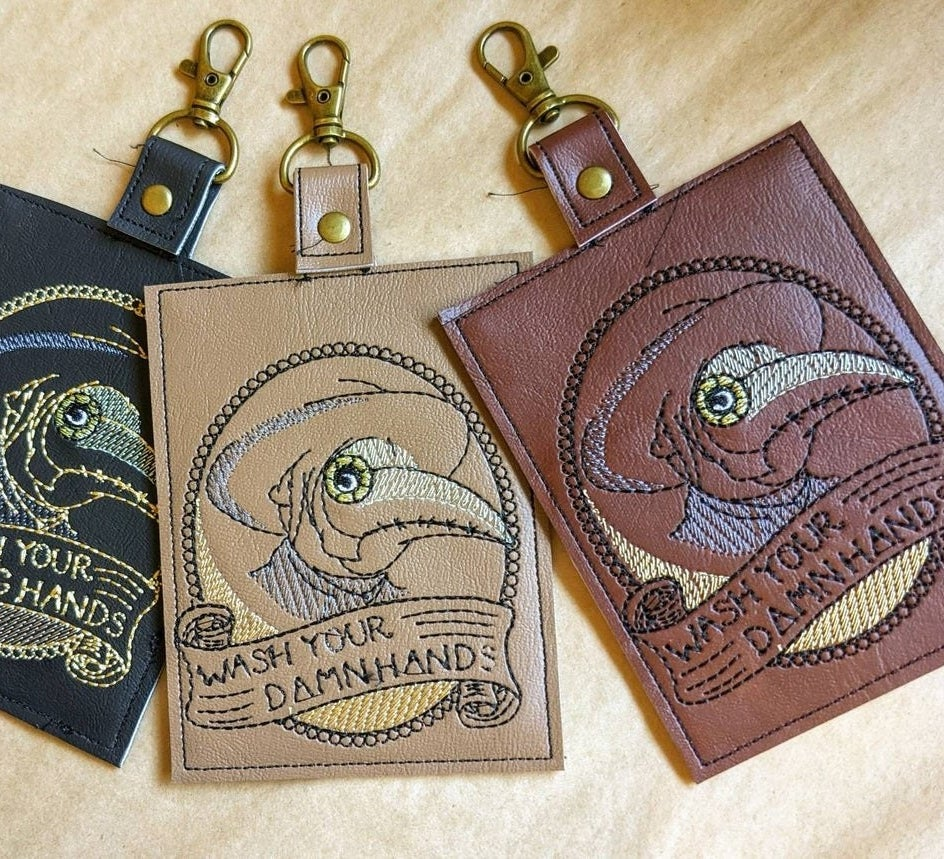 leather case with plague doctor that says wash your damn hands
