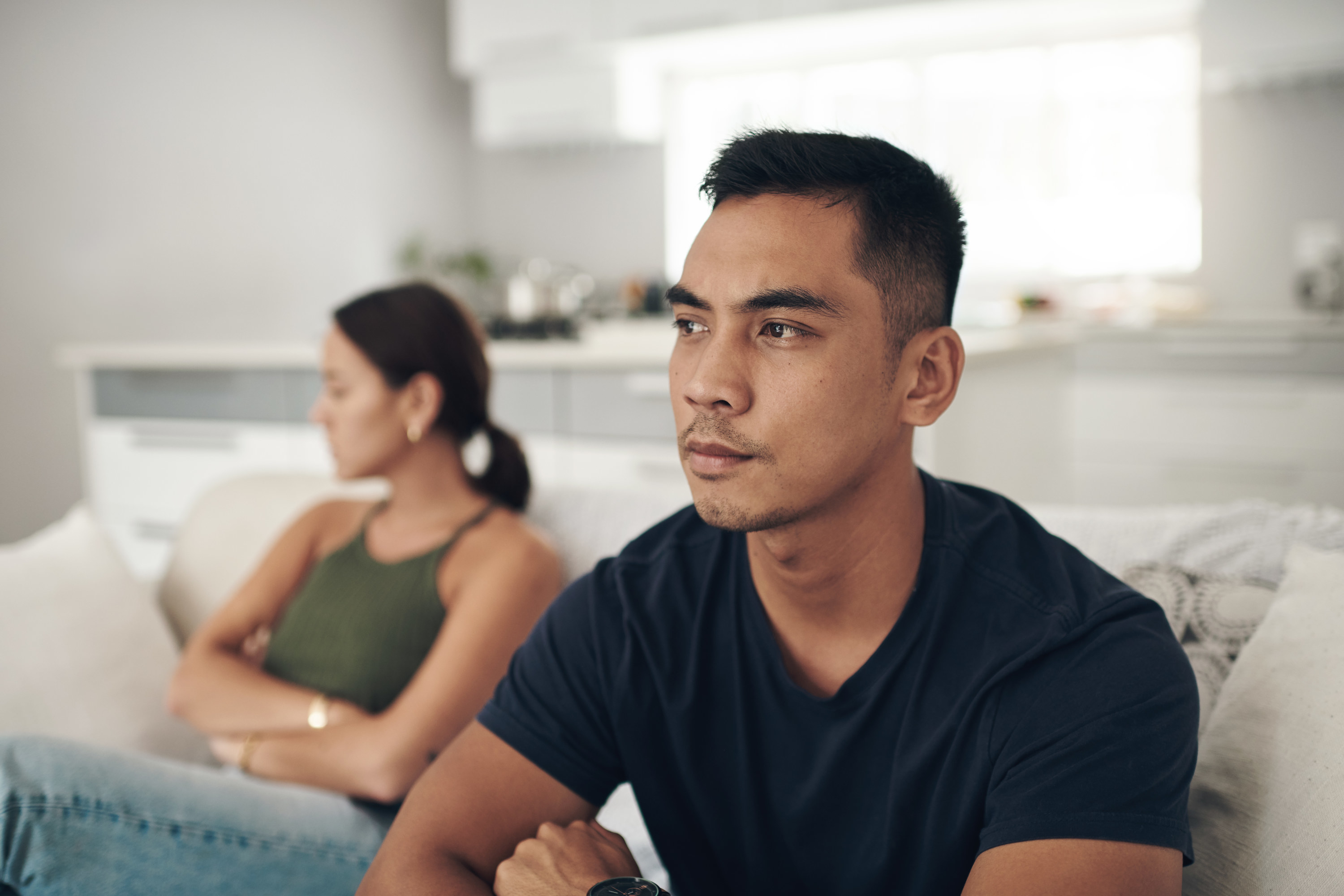Couple with their arms crossed looking away from each other