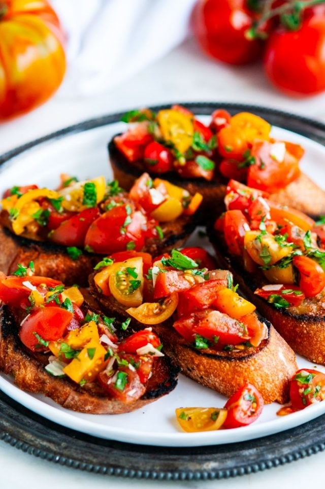 Bruschetta topped with colorful tomatoes and basil.