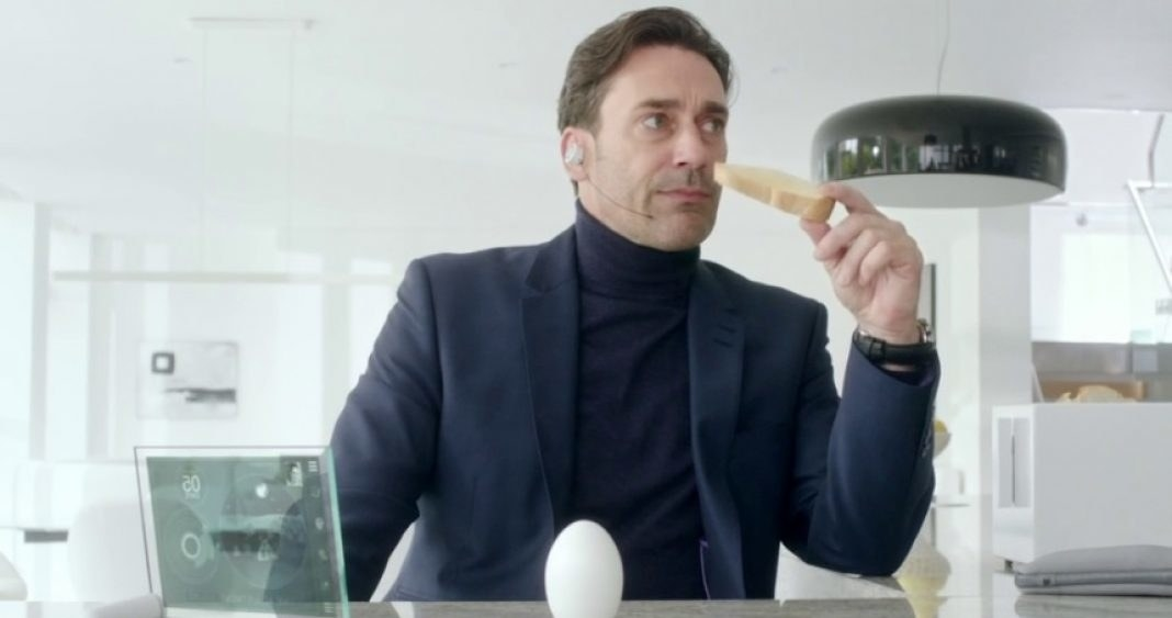 a man in a turtleneck and blazer wears an earpiece and bites into a piece of toast