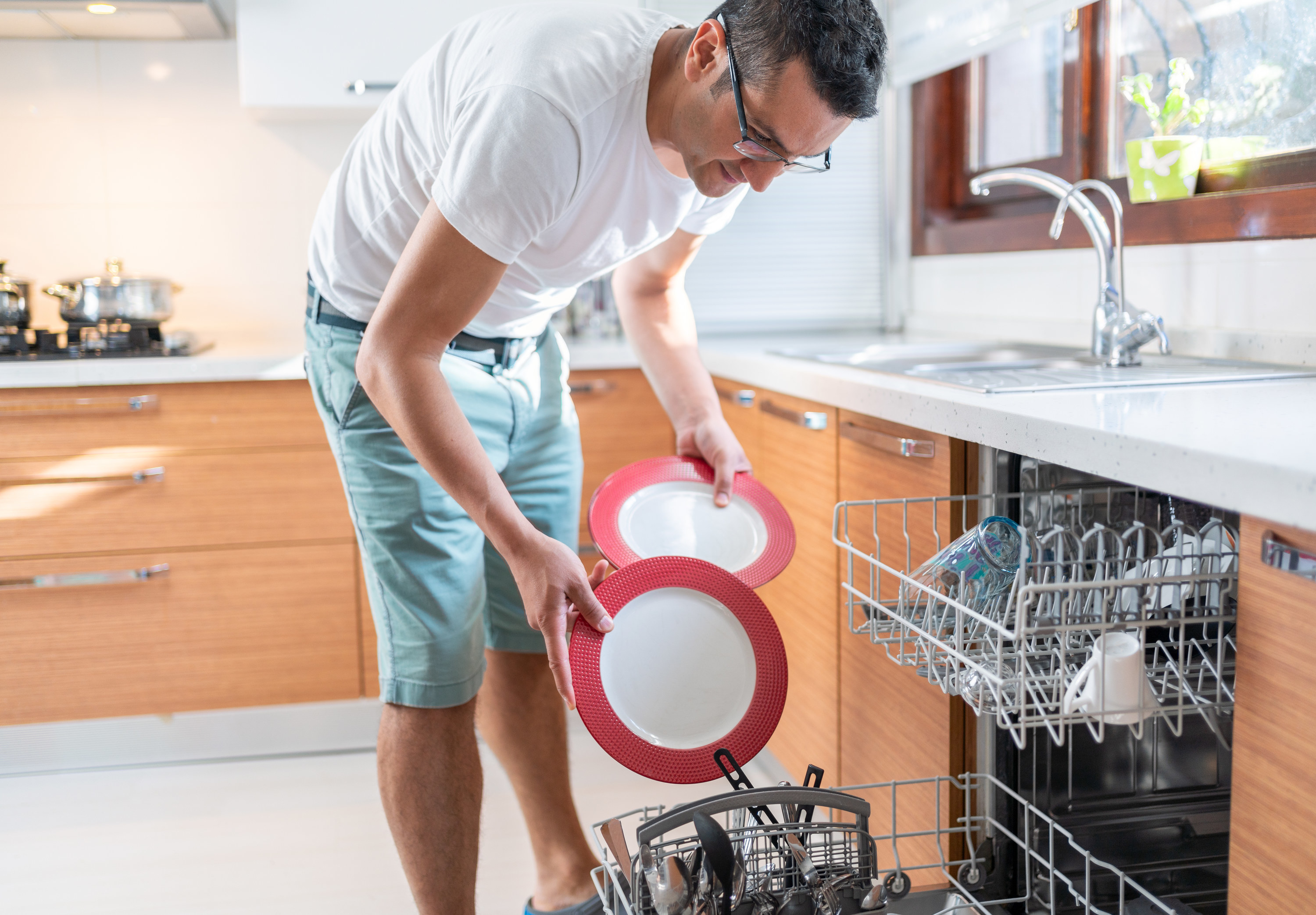 A person loading the dishwasher