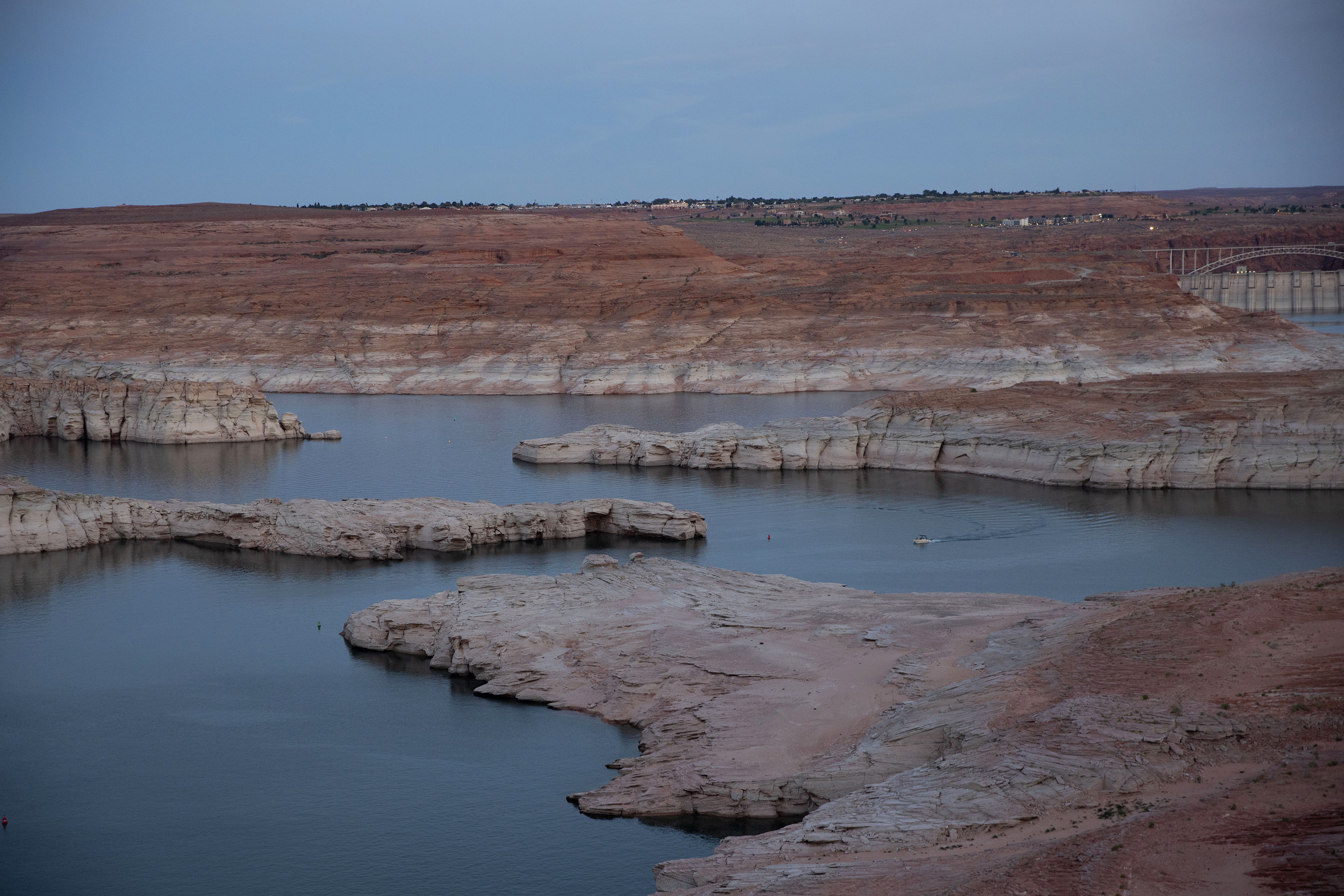 Low water levels are seen at dusk in Lake Powell with urban development in the background as a boat moves through the body of water