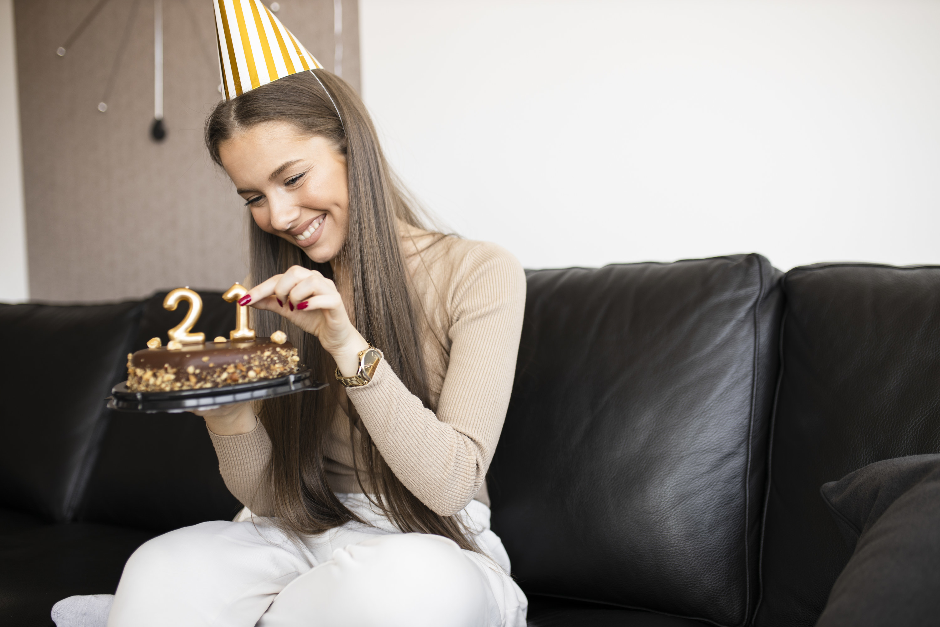 A person holding a cake to celebrate their 21st birthday