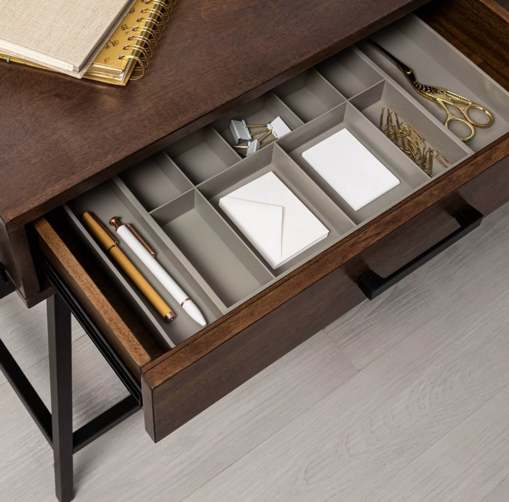 A gray expandable drawer organizer in an office desk drawer filled with pens and other office supplies