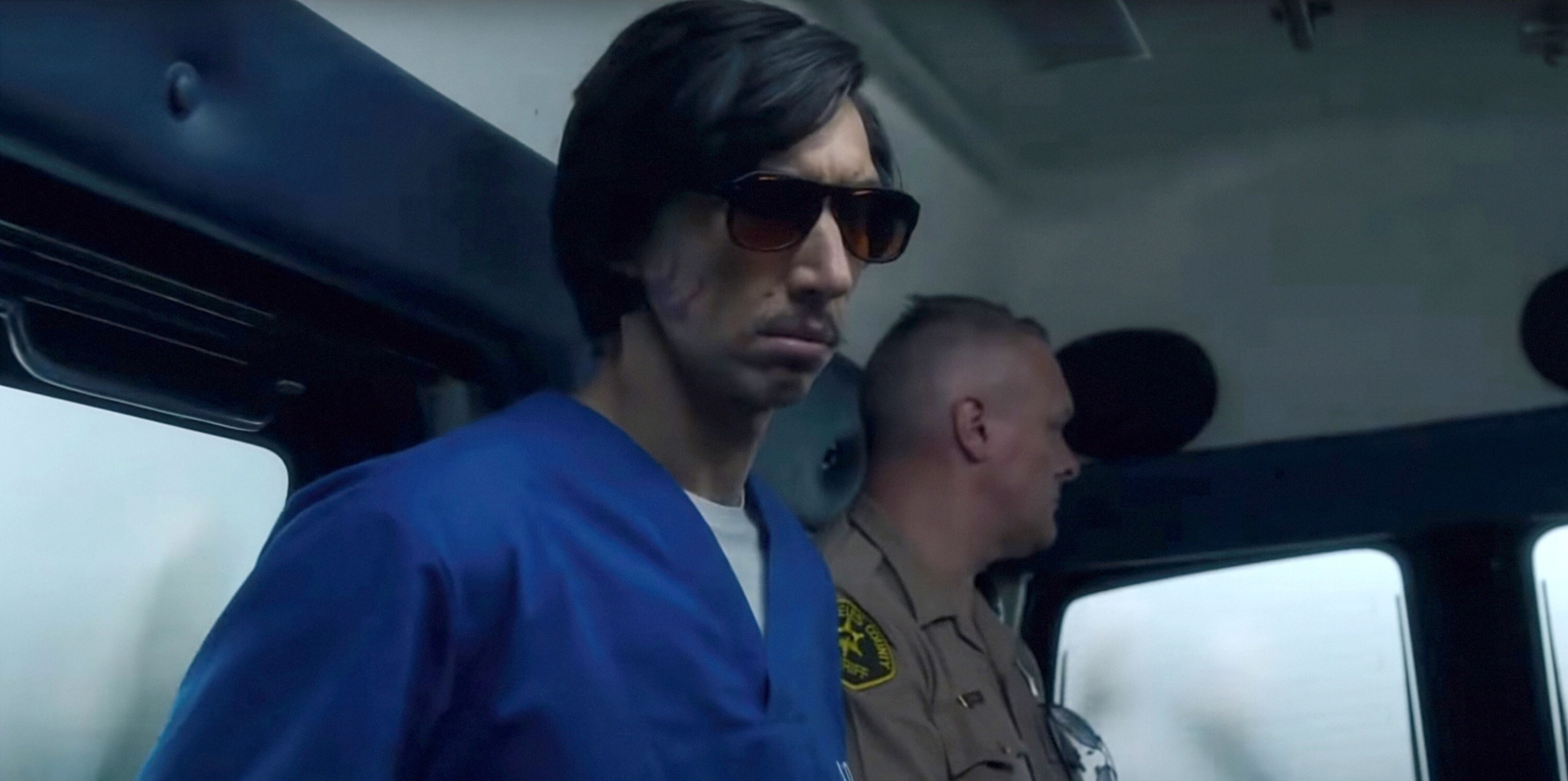 Adam Driver wears sunglasses in the back of a van