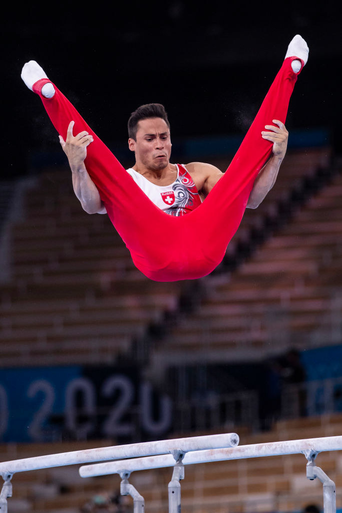 The gymnast is holding onto his legs in the v-position